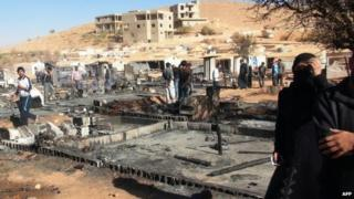 People walk past the charred remains of tents at a refugee camp outside Arsal, Lebanon (25 September 2014)