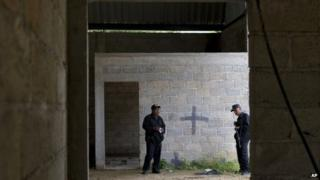 Mexican state police on 3 July 2014 inside a warehouse where a shootout between Mexican soldiers and alleged criminals on the outskirts of the village of San Pedro Limon, in Mexico state, Mexico