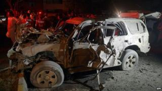 A wrecked car sits at the site of a bomb attack targeting a senior police officer in Karachi on September 25, 2014