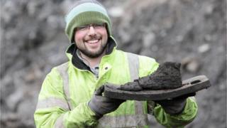 Archaeologist Stephen McLeod holds a wooden shoe last dating back to early medieval times.