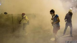 Protesters in face masks take refuge as police fire tear gas at a pro-democracy demonstration in Hong Kong