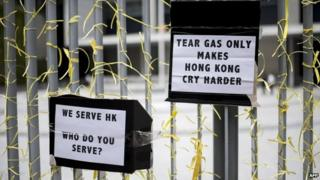 "Signs that read ""Tear gas only makes Hong Kong cry harder"" and ""We serve HK; who do you serve?"" are seen tied to a fence in front of the central government offices in Hong Kong on 30 September 2014"