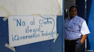 A Clorox worker stands next to a sign on a door at the company headquarters in Valles del Tuy, in Miranda state on 26 September, 2014.