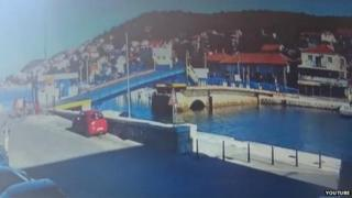 Still from video of woman driving her car over an open drawbridge in Tisno, Croatia
