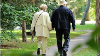 An older couple walk holding hands