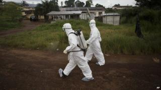 Health workers in protective suits in Sierra Leone