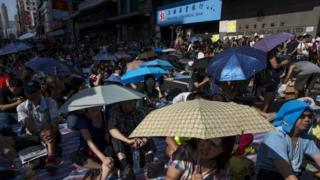 Protesters sit under umbrellas at a main street at Mongkok shopping district