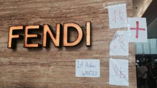 Signs for a first-aid stand are stuck on the Fendi store on Canton Road, Hong Kong on 1 Oct