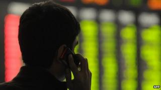 Stockbroker talking on the phone with stocks and shares prices in the background
