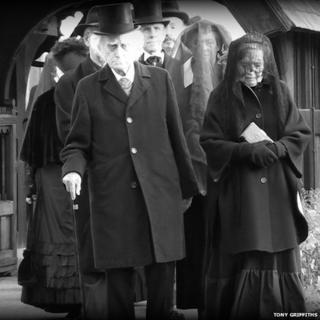 Actors portray the funeral scene