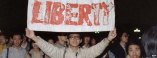 A student displays a banner with one of the slogans chanted by the crowd in Tiananmen Square on 22 April 1989
