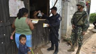 Residents watch information released by a joint patrol of marines, army, ministerial policemen and relatives of young that went missing during weekend clashes in Iguala, Guerrero state, Mexico on October 1, 2014
