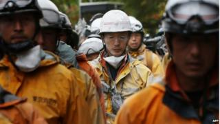 Firefighters come down from Mount Ontake at Otaki village at Nagano prefecture on 2 October 2014, five days after the volcano erupted