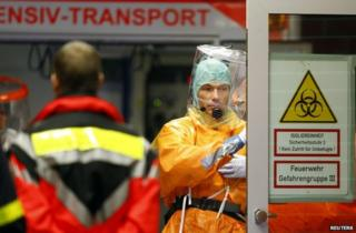 Medical staff in protective equipment attend the arrival of an Ebola patient at Frankfurt University Hospital, 3 October