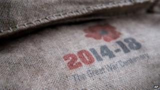 """A sandbag marked with a poppy emblem bearing the words: """"2014-18: The Great War centenary."""""""