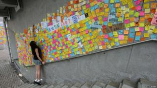 A young woman looks at messages of support