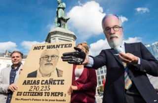 Protesters mock Spain's Miguel Arias Canete in front of the European Parliament in Brussels, 1 October