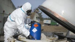A Worker in protective clothing unloads a dummy grenade during a press day at the GEKA facility on 5 March 2014 in Munster, Germany.