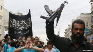 Supporters of the al-Nusra Front take part in a protest in Aleppo, Syria, against President Bashar al-Assad and the international coalition against Islamic State and other Islamist groups, on 24 September.