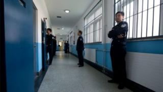Police guards stand in a hallway inside the No. 1 Detention Centre during a government guided tour in Beijing on 25 October 2012.