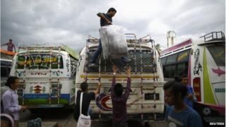 People load their luggage on top of a long distance bus heading to their village for Dashain, Hinduism's biggest religious festival, at the bus station in Kathmandu 24 September 2014
