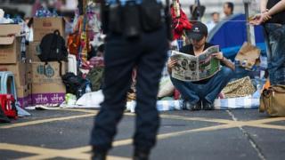 Pro democracy protester reads a newspaper at Hong Kong's Mongkok district