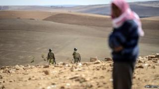 A Syrian Kurd stands as Turkish soldiers patrol near the Syrian border around Suruc on 30 September 2014.