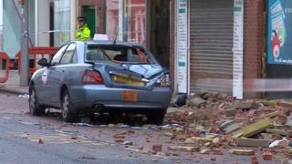 Crushed car surrounded by bricks, rubble and masonry