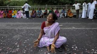 A supporter of former Tamil Nadu chief minister Jayaram Jayalalitha wails sitting on a road after a court rejected Jayalalitha's plea for bail in Chennai, India, Tuesday, Oct. 7, 2014.