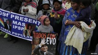 "A child holds a poster of Bolivia""s President Evo Morales during a presidential election campaign meeting in La Paz"