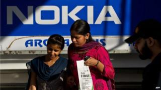 Indian women walk out of a Nokia store in New Delhi