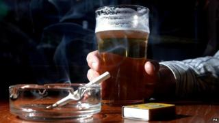 Man holding pint of beer and lit cigarette in ashtray