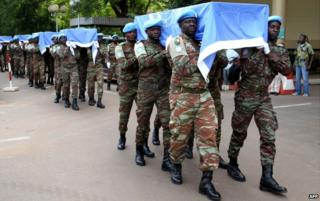 UN peacekeepers carry carry the coffins of nine UN soldiers, who were killed by Islamist militants, at a ceremony in Mali - October 7, 2014