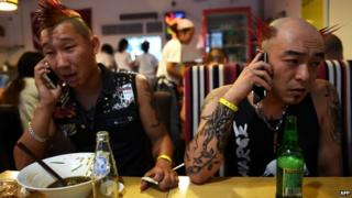 Punk band The Demonstrators make phone calls while having dinner before their performance at the Beijing Punk Festival