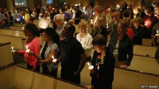 People hold candles during a a prayer vigil and memorial at Wilshire Baptist Church in Dallas, Texas, on 8 October 2014