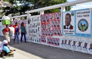 People walk pass a wall adorned with various election campaign posters in Maputo, Mozambique, 02 October 2014.