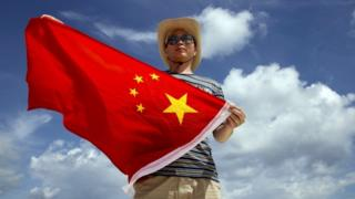 Police officer poses with a Chinese national flag on the Quanfu island.
