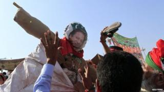 """Anti-government supporters beat an effigy of Pakistan""""s Prime Minister Nawaz Sharif after attending Eid al-Adha prayers outside the parliament house in the Red Zone during anti-government protest in Islamabad October 6, 2014."""