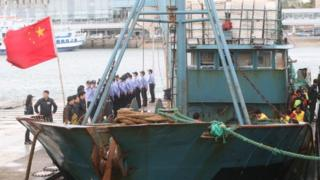 South Korean coastguard officers stand on guard after a Chinese fishing boat arrived in the southwestern port of Mokpo on October 17, 2012, a day after it was seized for illegal fishing