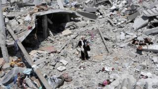 A woman walks on the rubble of destroyed houses in the Khazaa neighbourhood of Khan Younis in southern Gaza
