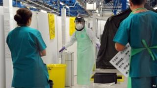 Two people in medical uniforms look at a person in full protective gear for an Ebola drill