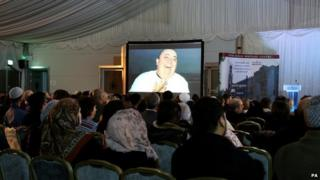 The face of Alan Henning shown on a big screen at the British Muslim Heritage Centre in Manchester