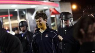 A demonstrator protesting the shooting death of Michael Brown and 18-year-old Vonderrit Myers Jr. reacts to a self defence spray used by police in riot gear in St. Louis, Missouri, 12 October 2014