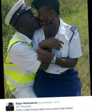 Two Tanzanian police officers kissing