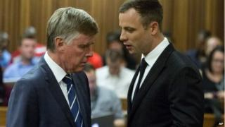 Oscar Pistorius talks with one of his defence lawyers in Pretoria, South Africa 13 Oct 2014