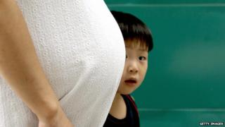 a South Korean child stares behind a belly of his pregnant mother