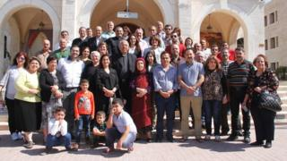 Iraqi Christian refugees pose with speakers from Jordanian Catholic and Muslim institutions coming to their aid in Amman