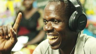Smiling man with headphones on, in a studio