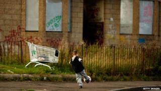 Child playing football in front of boarded up homes in Glasgow
