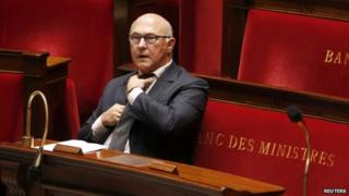 French Finance Minister Michel Sapin adjusts his tie at the start of budget debates in the National Assembly. Photo: 14 October 2014